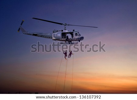 Helicopter landing at sunset - stock photo
