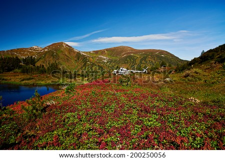 Helicopter landing in the mountains of Siberia  - stock photo
