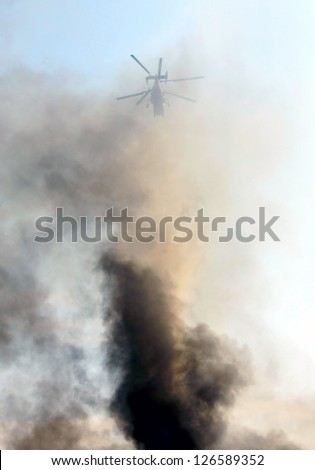 Helicopter on blue sky in black smoke. - stock photo