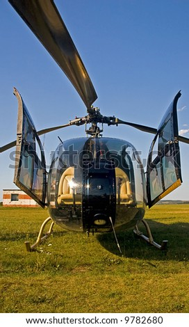 Helicopter on green grass, front view - stock photo