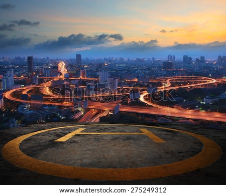 helicopter pad on top building roof against beautiful express way and land transportation in dusky sky city scape  - stock photo