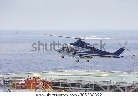 Helicopter parking at an offshore oil and gas platform to receive passenger and cargo to onshore. - stock photo