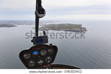 Helicopter scenic flight view from cabin dashboard with gauges aerial panorama of underlying Sydney Harbour North Head and residential suburbs - stock photo