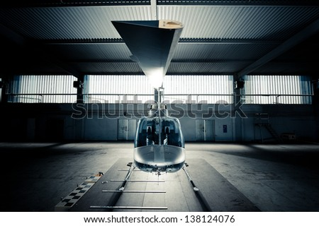 Helicopter standing in hangar on a platform - stock photo