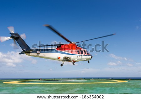 Helicopter taking off from jack up oil rig helipad with blue sky - stock photo