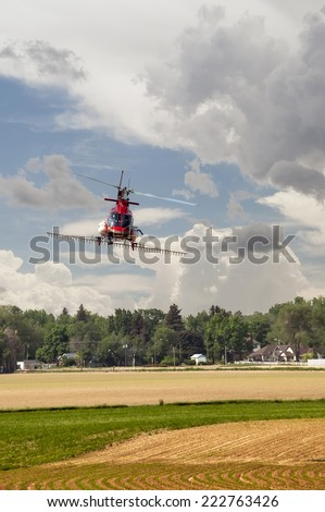 Helicopter used for crop dusting, spraying fertilizer on a field in northern Colorado, USA. - stock photo