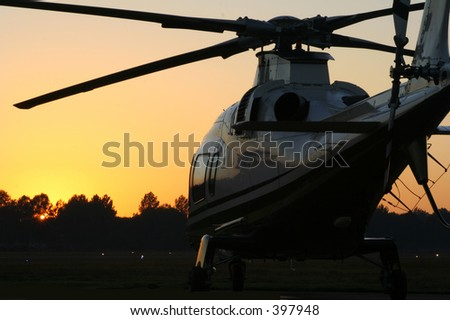 Helicopter waiting for takeoff at sunrise - stock photo