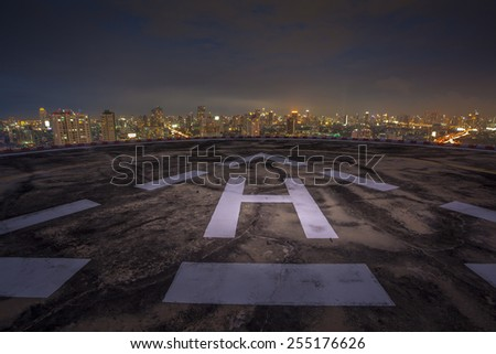 Helipad on the roof of a skyscraper at night with cityscape view - stock photo