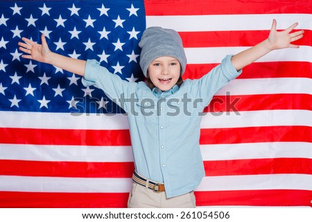 Hello America! Little boy in eyewear keeping arms raised and smiling while standing against American flag - stock photo