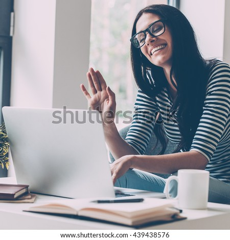 Hello! Cheerful young beautiful woman waving while looking at her laptop and sitting at her working place  - stock photo