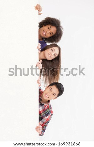 Hello! Cheerful young multi-ethnic people looking out of copy space and smiling at camera while isolated on white - stock photo