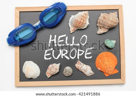 Hello Europe text on chalk board with swimming goggle and shell - vacation and business concept - stock photo