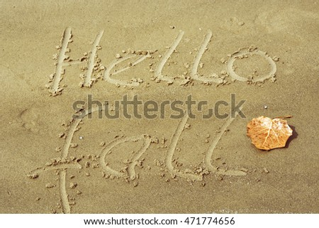 hello fall written on the sand, yellow leaf. Autumnal Background. sun light effect, toned image