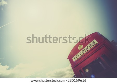 Hello from London, England. Classic iconic vintage English old telephone box with bright sun in sky creating lens flare with copy space for text. - stock photo