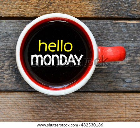 Hello monday./ Inscription hello monday in a cup of coffee and wooden background.