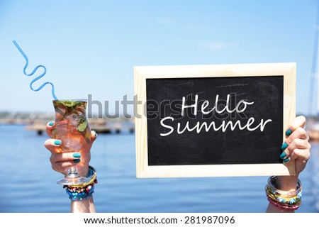 Hello summer concept. Chalkboard in female hand on beach background - stock photo