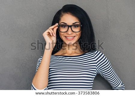 Hello there! Beautiful young African woman looking at camera with smile and adjusting her glasses while standing against grey background - stock photo