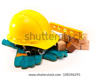 Helmet builder, work gloves and a bubble level lying on wooden cubes on a white background