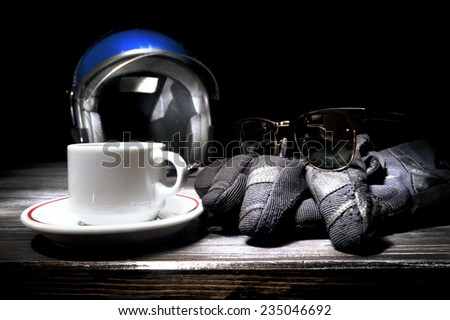 Helmet gloves and cup of coffee on table - stock photo