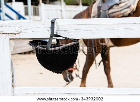 Helmet jockey weigh on wooden cross beam fence site - stock photo