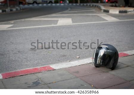 Helmet on sidewalks with background is blur of street. - stock photo