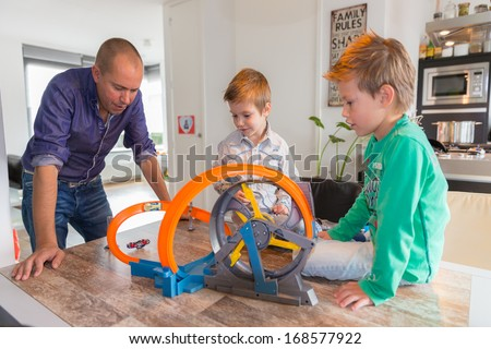 HELMOND, NETHERLANDS - OCTOBER 5, 2013: Children playing with a race track whilst the father is watching.  - stock photo