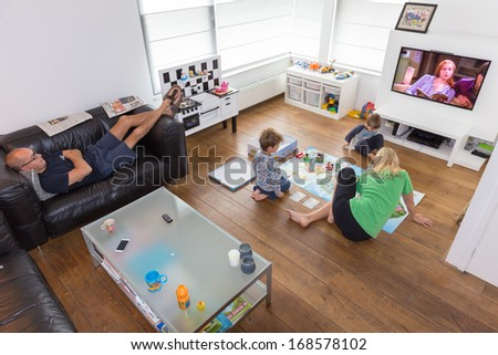 HELMOND, NETHERLANDS - OCTOBER 5, 2013: Mother playing a game with her children whilst the father is watching television. - stock photo