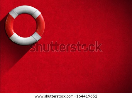 Help Concept - Red and White Lifebuoy / Red and white lifebuoy hanging to a red velvet wall - Concept of help - stock photo
