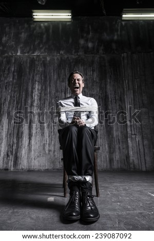 Help me! Shocked businessman sitting at the chair and shouting while being tied up  - stock photo