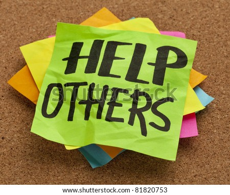 help others reminder on sticky note posted on a cork board - stock photo
