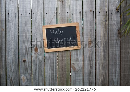 Help wanted blackboard sign on a backyard fence