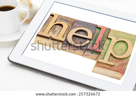 help word typography - text in letterpress wood type blocks on a digital tablet with a cup of coffee
