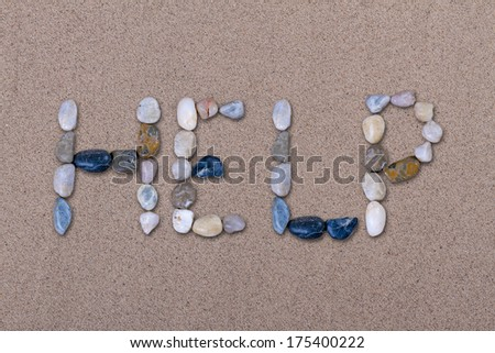 Help Written with Pebbles on Sand - stock photo