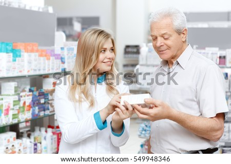 Helpful pharmacist. Cheerful young woman pharmacist assisting her senior client at the drugstore health medicine healthcare vitality helpful specialist drugstore shopping concept
