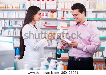 Helpful pharmacist serving and consulting man at pharmacy  - stock photo