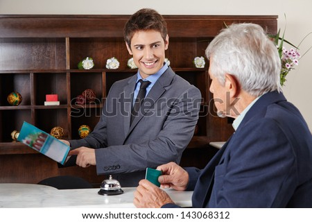Helpful receptionist in hotel showing city map to senior guest - stock photo