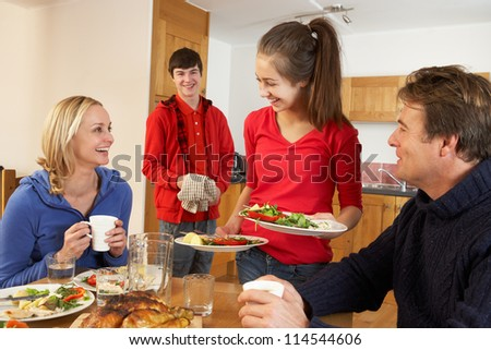 Helpful Teenage Children Serving Food To Parents In Kitchen - stock photo