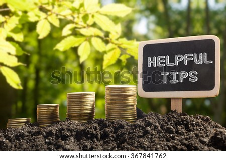 Helpful tips - Financial opportunity concept. Golden coins in soil Chalkboard on blurred urban background - stock photo