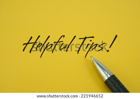 Helpful Tips! note with pen on yellow background - stock photo