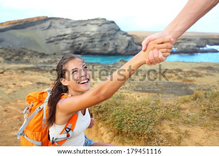 Helping hand - hiker woman getting help on hike smiling happy overcoming obstacle. Tourist backpackers walking on Green Sand Beach, Papakolea on Big Island, Hawaii, USA. Young couple traveling. - stock photo