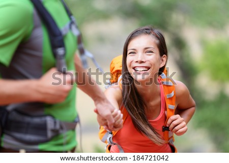 Helping hand - hiking woman getting help on hike smiling happy overcoming obstacle. Active lifestyle hiker couple traveling. Beautiful smiling mixed race Asian Caucasian female model. - stock photo