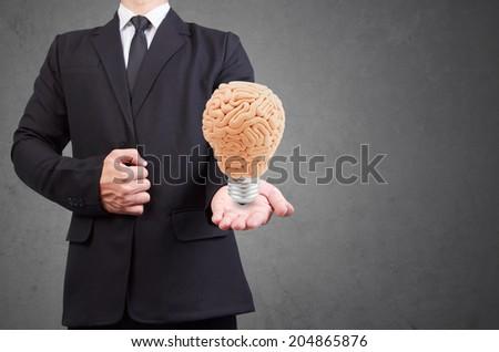 helping hand holding brain as light bulb idea concept for creativity - stock photo