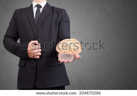 helping hand holding side view human brain idea concept for creativity against concrete wall - stock photo