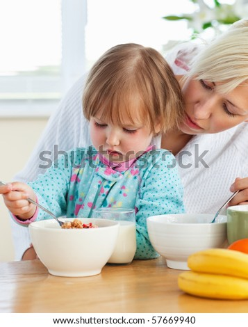 Helping mother and daughter having breakfast in the kitchen - stock photo
