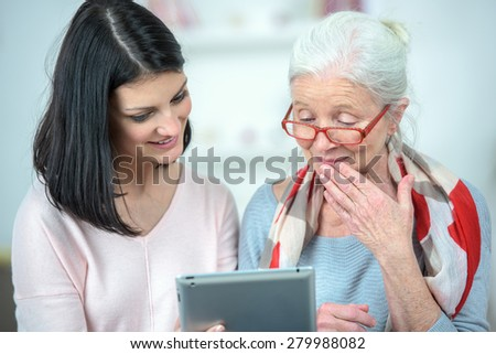 Helping old woman use a tablet computer - stock photo