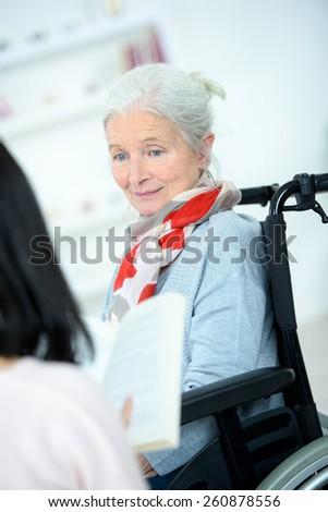 Helping senior woman to read - stock photo
