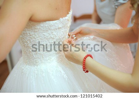 helping to lace up bride's wedding dress - stock photo