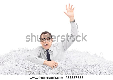 Helpless man drowning in a pile of shredded paper isolated on white background - stock photo