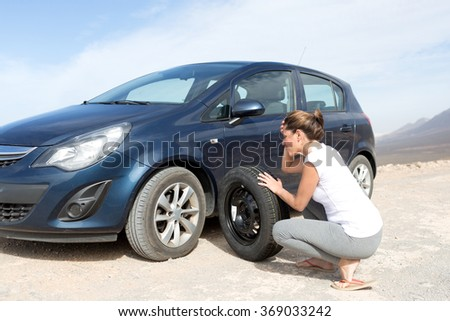 Helpless woman changing tires - stock photo