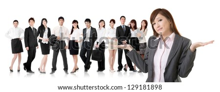 Helpless young business woman shrugs her shoulders in front of her team on white background.
